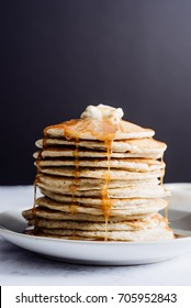 A tall stack of golden pancakes layered on a gray plate with melted butter and syrup dripping down the sides of the stack.