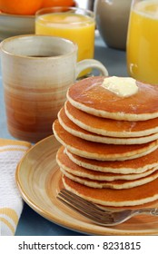 A tall stack of pancakes covered in butter and syrup