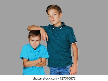 A tall teenage boy put his arm on the head of an angry small boy.