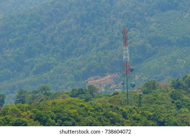 A tall telecommunication tower is standing in amid the green valley background. A telecom tower in a rural area needs off-grid power to transmit cell signals.
