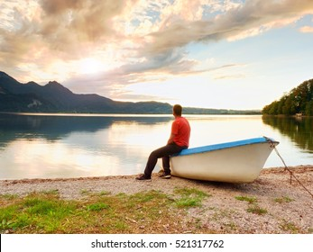 Tall tired man in red shirt sit on old fishing paddle boat at mountains lake coast. Afternooon sun hidden in clouds above mountain peaks. Vintage photo effect