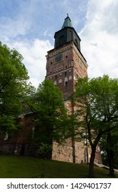 The tall tower of the historic medieval Gothic Cathedral of the 13th century and the park around Turku Abo on a summer day in Finland. Bottom view of the historic Lutheran Cathedral in Turku.