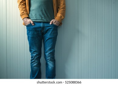 Tall unrecognizable casual man in jeans posing, wall as copy space.