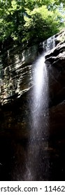 tall waterfall cropped narrow bright sunlight and long drop from cliff and Forrest above