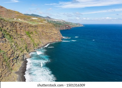 Tall waves at Playa de Nogales beach in La Palma, Spain. High angle view  from an observation point on the cliff with some tourists.