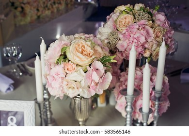 Tall white candles stand around little pink bouquets in silver vases
