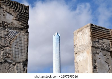 Tall White Concrete Chimney seen between  Rough Concrete Pillars against Blue Sky