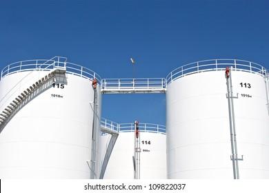 Tall white oil storage tanks