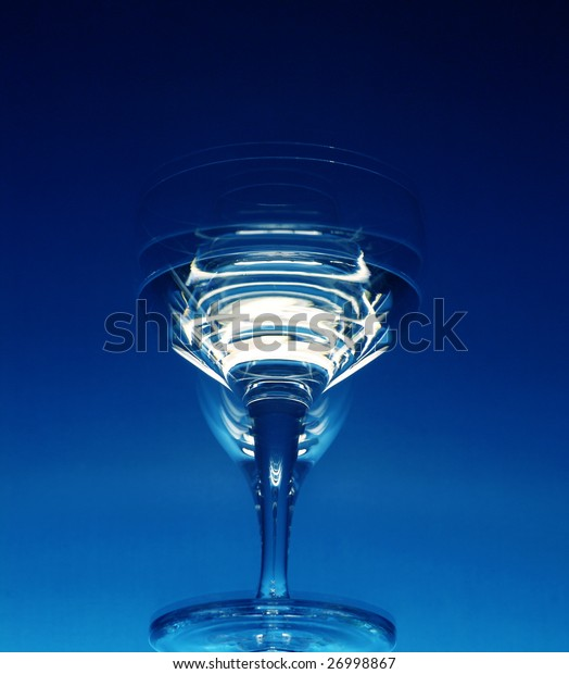 Tall wineglasses against a dark blue background