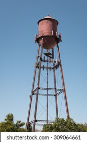 A tall wireless antenna tower designed to appear like a water tower