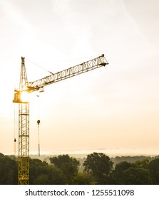 Tall yellow tower crane at a construction site amid morning sun and fog