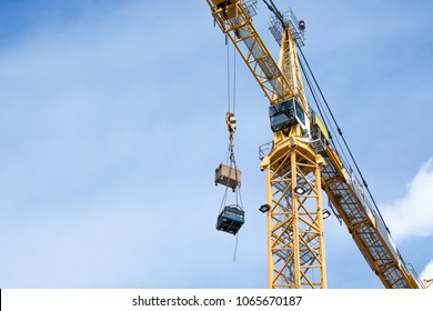 Tall yellow tower crane, with metal support scaffolding, lifting boxes on pulley cables, with a blue sky clouds background