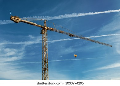 tall yellow working crane on blue cloudy sky background