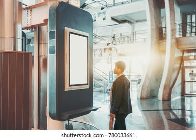 Tall young black African American girl in contemporary airport terminal is standing in front of vertical blank departures and arrival information LCD board mockup to check her flight info
