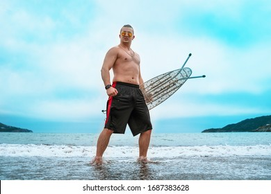 Tall young man with a naked torso and ironing board in hand standing on beautuful sea landscape background. Blue sky, little waves, parody of surfers, outdoors.