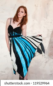 Tall young redhead in a blue, black and white dress