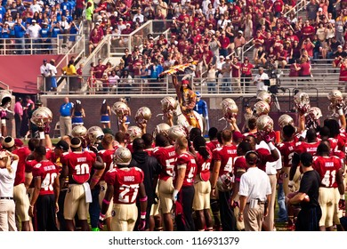 TALLAHASSEE, FL - OCT. 27:  Seminole players hold helmets high as Chief Osceola prepares to throw the spear to start the FSU vs Duke football game, at Doak Campbell Stadium on Oct. 27, 2012.