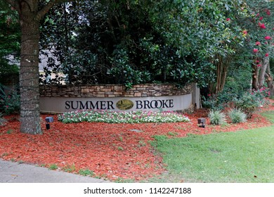 Tallahassee, FL, USA - July 14, 2018: Neighborhood sign of Summer Brooke community in northeast Tallahassee. Summer Brooke neighborhood community sign on a wall near foliage and flowers in the day.