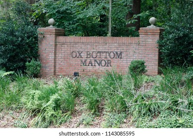 Tallahassee, FL, USA - July 14, 2018: Ox Bottom Manor neighborhood wall sign with two pillars near foliage. Leon County suburban neighborhood sign of Ox Bottom Manor west of Thomasville Road.