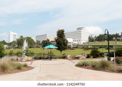 Tallahassee, FL, USA - July 15, 2018: Public Cascades Park with a downtown view of Tallahassee in the distant background. Cascades Park located southeast of downtown Tallahassee shown in the distance