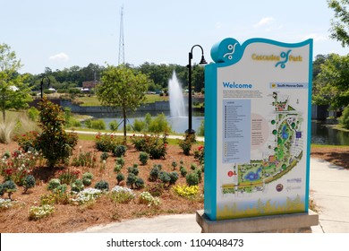 Tallahassee, FL, USA - May 13, 2018: Cascades Park entrance sign and landscape.View of Cascades Park beautiful landscape with lake fountain. Sunny day at Cascades Park in Tallahassee with sign and map