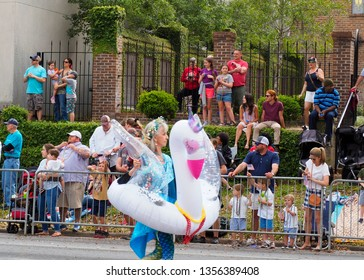 Tallahassee, FL/USA - March 30, 2019:  Woman marching parade dressed as a fairy godmother in a swan pool float