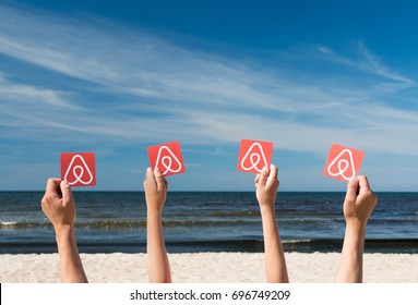 Tallin, Estonia - August, 2017: A man and a teenager hold printed cards with the logo of the famous booking sistem Airbnb. Sea, blue sky and beach with golden sand in the background.