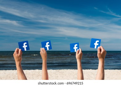 Tallin, Estonia - August, 2017: A man and a teenager hold printed cards with the logo of the famous social network Facebook. Sea, blue sky and beach with golden sand in the background.
