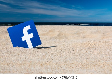 Tallin, Estonia - August, 2017: Printed on paper logos of the famous social network Facebook. In the background, the sea, the blue sky and golden sand. Concept. Summer. Recreation. Vacation.