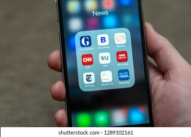Tallinn / Estonia - 01/19/2019: Male hand holding Black Apple iPhone with icons of News media: Guardian, Bloomberg, BBC News, CNN, NY Times, Euronews and other application on screen. News media icons.