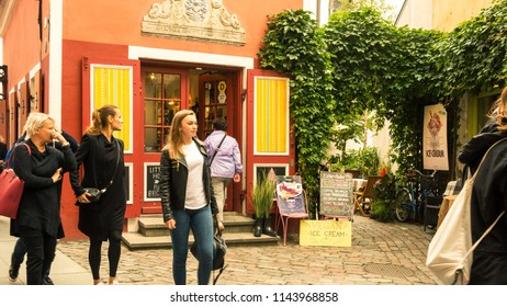 Tallinn / Estonia - 230717: Tourists stroll by an independent shop in Tallinn's colourful central market district in summer