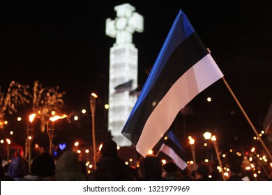 Tallinn, Estonia - 24 February 2019 - Estonian flags at torchlight procession at Estonian Independence day in Tallinn freedom square with Estonian freedom Cross and torches on the background