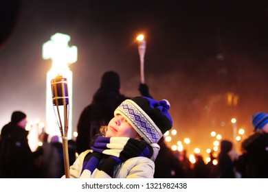 Tallinn, Estonia - 24 February 2019 - Small girl taking part of torchlight procession at estonian Independence day in Tallinn freedom square with estonian freedom cross in the background
