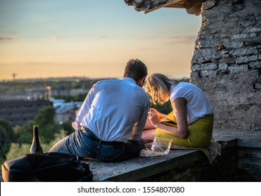 Tallinn, Estonia - 29.07.2017 Picnic at Tallinn tower. couple sitting together looking at mobile