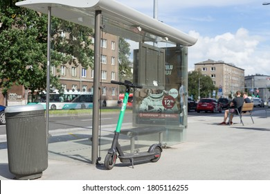 Tallinn / Estonia - August 24 2020:  Bolt electric scooter (also e-scooter) parked behind bus stop in the center of capital Tallinn. Affordable, easy ride around town enabling micromobility.