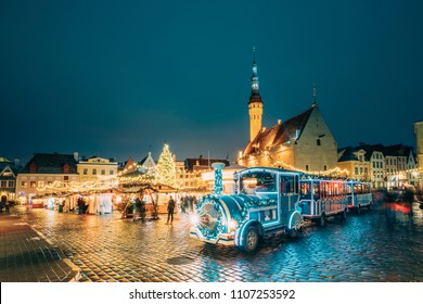 Tallinn, Estonia. Beautiful Train for Sightseeing Near Traditional Christmas Market On Town Hall Squar. Christmas Tree And Trading Houses. Famous Landmark.