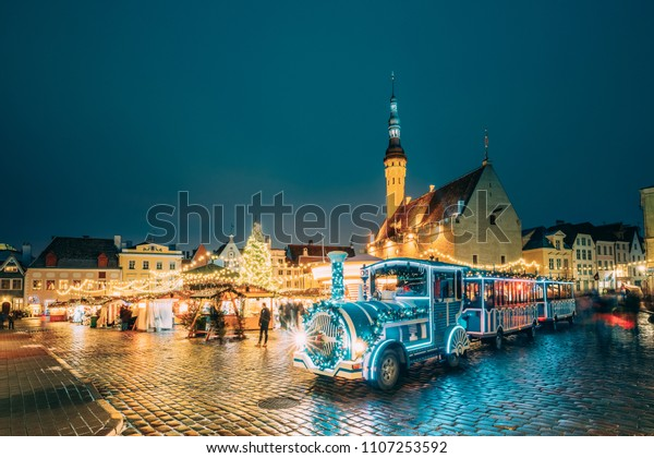 Tallin, Estonia. Hermoso tren para hacer turismo cerca del tradicional mercado navideño en la Plaza del Ayuntamiento. Árbol De Navidad Y Casas Comerciales. Famoso monumento.