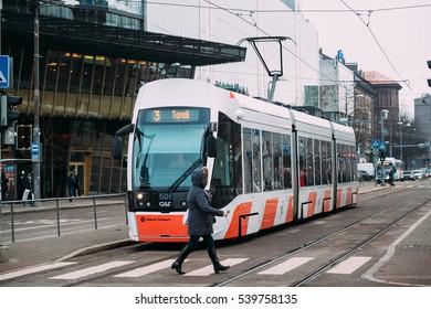 Tallinn, Estonia - December 2, 2016: Woman crossing road at a pedestrian crossing on tramways before staying tram.