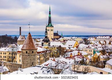 TALLINN, ESTONIA - February 2018: Panoramic view of Tallinn old town on cloudy winter day. Tallinn roofs covered with snow, Old town Tallinn, Estonia