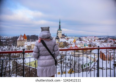 TALLINN, ESTONIA - February 2018: Panoramic view of Tallinn old town on cloudy winter day. Tallinn roofs covered with snow, Old town Tallinn, Estonia. Woman warmly dressed looking at old town.