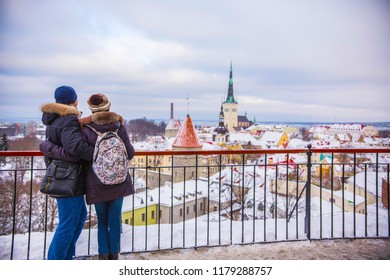 TALLINN, ESTONIA - February 2018: Young couple together looking at Tallinn old town aerial view on cloudy winter day. Tallinn roofs covered with snow, Old town Tallinn, Estonia