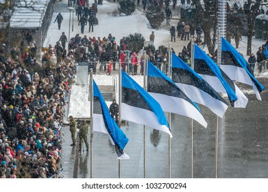 Tallinn, Estonia - February 24, 2018: Crowd of people celebrating 100 years of Estonia Independence at Freedom square in the old town. Military parade. 6 national flags waving in the wind. Top view.