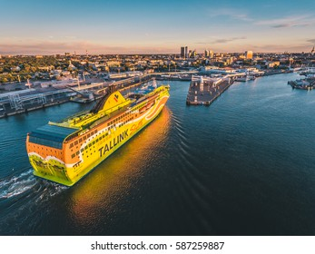 TALLINN, ESTONIA - JULY 2016: Aerial shot of the Tallink Shuttle MS Superstar cruise ferry arrives at port of Tallinn. Tallinn cityscape on the background at sunset.