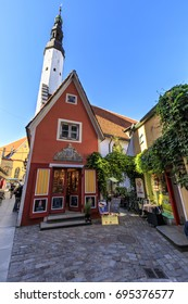 TALLINN, ESTONIA - JULY 26, 2017: Red building facade and tall tower of church of Holy Spirit in the old town of Tallinn, Estonia on July 26, 2017