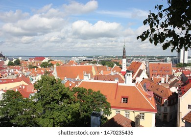 Tallinn, Estonia - July 3, 2019: Kohtuotsa viewing platform on Toompea hill, best viewpoint, incredible view, panorama of Old Town red rooftops and towers, sunny day, blue sky and sea, green trees
