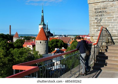 TALLINN, ESTONIA - JULY 7, 2017: Tourists enjoy the view of Oleviste church and old town of Tallinn from the observation platform on Toompea hill.
