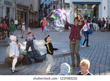 Tallinn, Estonia - June 13, 2016: Street artist performing with a huge bubble while people are watching the show