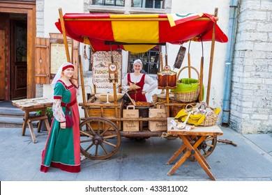 Tallinn, Estonia - June 2, 2016: Beautiful girls in national medieval dresses are selling nuts on a wooden cart in the Historical Center of Tallinn city. Tallinn, Estonia.