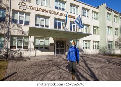 Tallinn, Estonia - MAR 14, 2020: A schoolboy in medical face mask is walking on square at school building