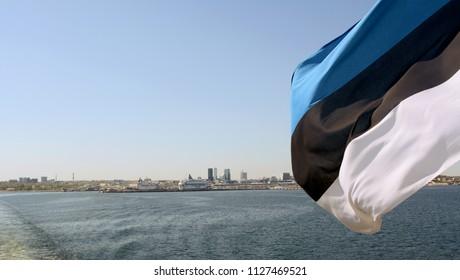 TALLINN, ESTONIA - May 13, 2018: Estonian flag flies from a ferry crossing the Gulf of Finland. Across the water is the cityscape of Tallinn, Estonia.